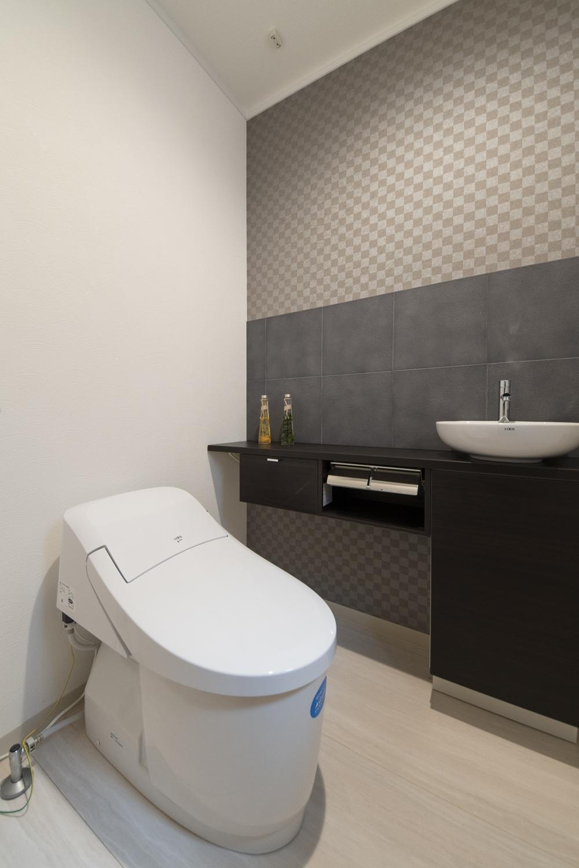 和のテイストのクロスと焼き物の味わいと土壁の質感を再現したエコカラットを施した、モダンな空間の1階トイレ。
