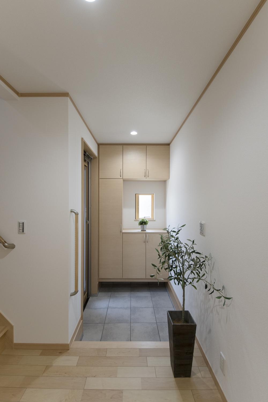 木の温もり感じるナチュラルテイストな玄関。小窓から光が差し込む明るい空間。手摺を設置して玄関の昇り降りをやさしくサポートします。