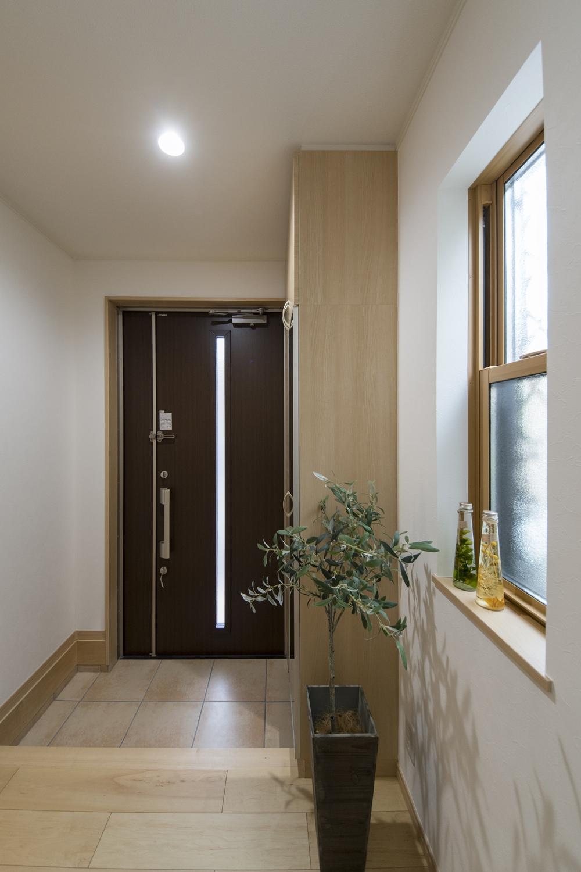 木の温もり感じる木目調のドアと収納、ベージュのテラコッタ調タイルが玄関をナチュラルな雰囲気に包みます。