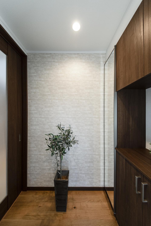 アクセントクロスをあしらい、深い色味の建具や玄関収納を設えたシックで大人な雰囲気の玄関ホール。
