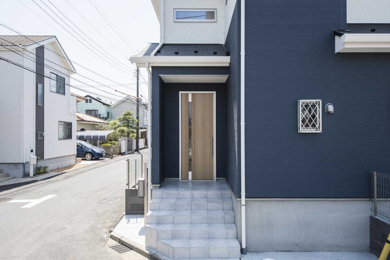 青空に映える「白×ブルー」のツートンカラーの外壁に、明るい木目調の玄関ドアを合わせた、ナチュラルモダンな雰囲気の外観。