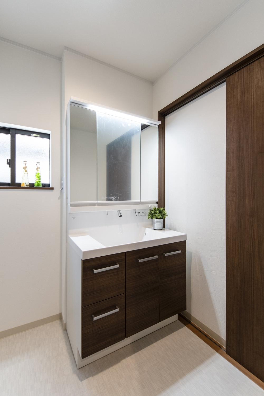 白を基調とした清潔感のある洗面室。洗面化粧台扉カラーをダークブラウンでアクセントにしました。