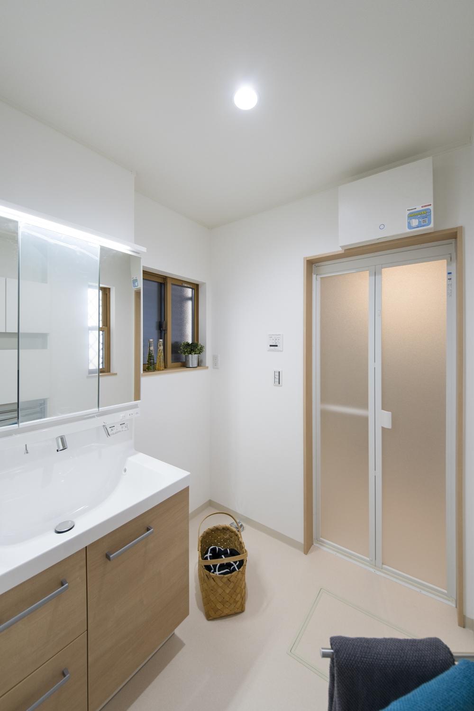 白を基調とした清潔感のあるサニタリールーム。洗面化粧台扉を明るい木目調カラーでアクセントにしました。