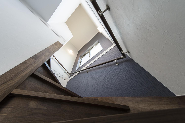 窓からの自然光とブラケットライトのやわらかい光が階段を照らします。ネイビー系のアクセントクロスが落ち着いた空間を演出。