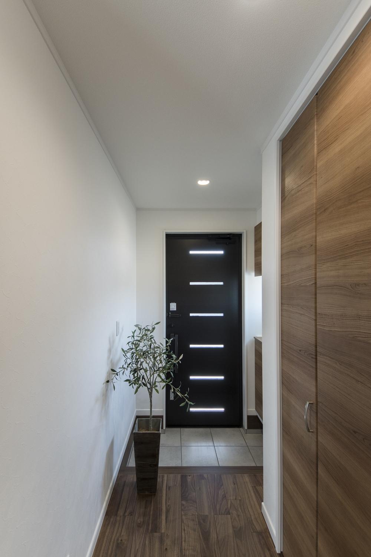 木の温もり感じるナチュラルテイストな玄関。ドアのガラス部分と小窓から自然光が差し込みます。