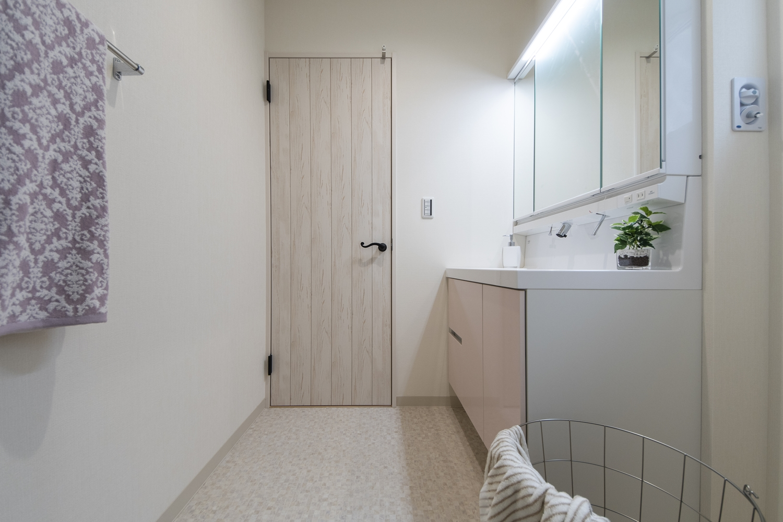 白を基調とした清潔感のあるサニタリールーム。洗面化粧台扉カラーをパステルピンクでアクセントにしました。