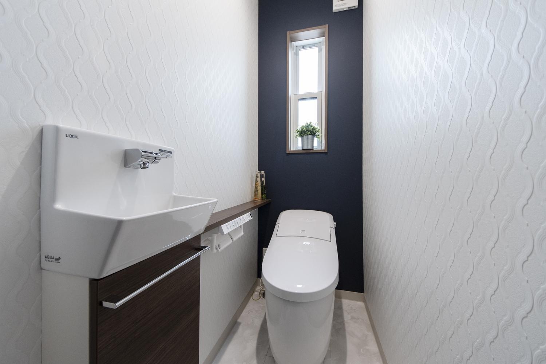 ダマスク柄の白クロスと、ネイビーのクロスを施したエレガントでおしゃれな空間のトイレ。