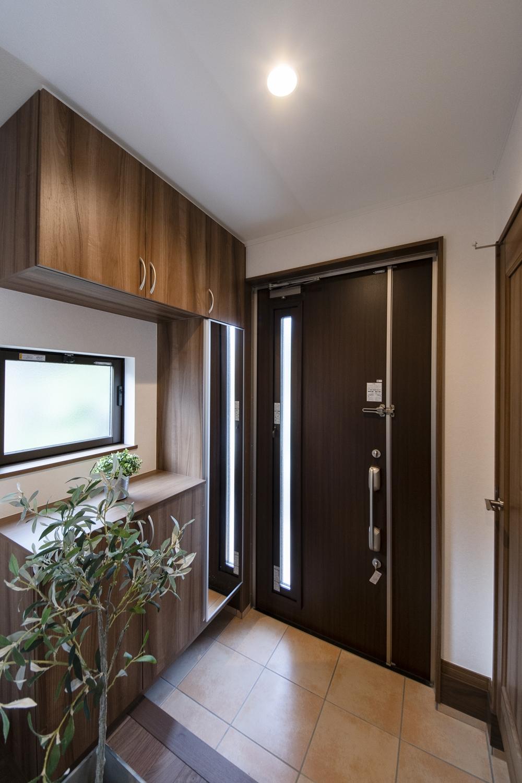 深みある木目カラーの玄関ドア・玄関収納が、上質で落ち着いた雰囲気を演出。