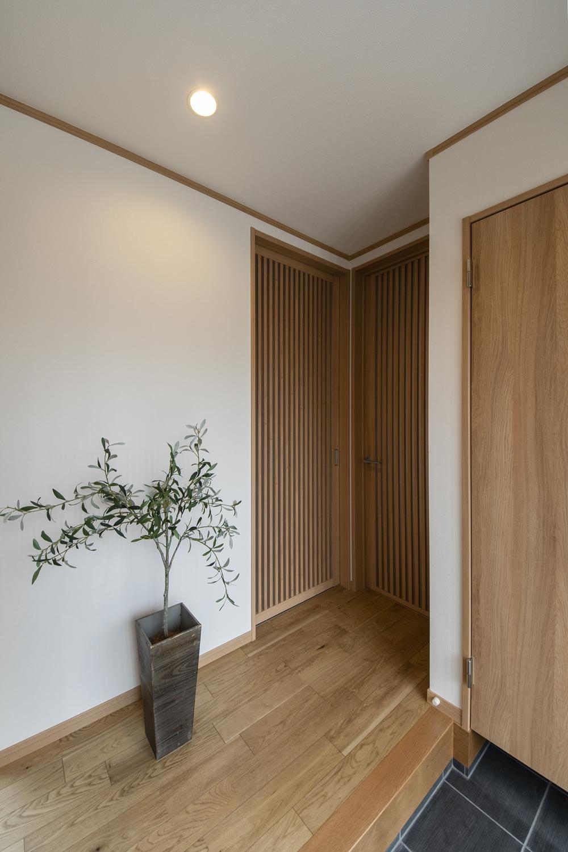 木の温もりを感じる、上質で落ち着いた印象の玄関ホール。無駄のないシャープなラインが気品を添える、スリット格子の建具が目を惹きます。