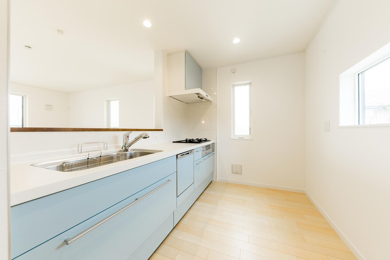 2階キッチン/爽やかなブルーのキッチン扉をアクセントにしました。囲むように設置された窓から、自然のやさしい光が降り注ぎます。