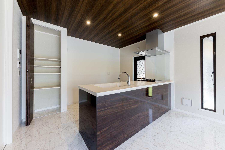 美しい光沢を放つダーク系木目カラーのキッチン。キッチン背面には扉付のパントリーを設置しました。