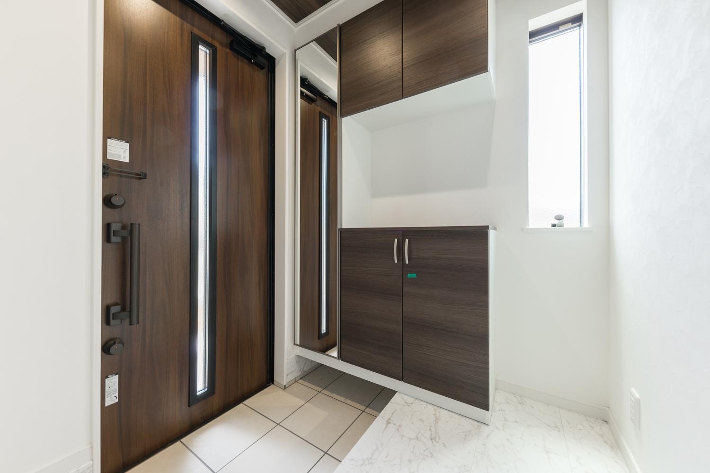 白い空間にダークトーンのドアや収納を差し色にした、美しいコントラストの玄関。