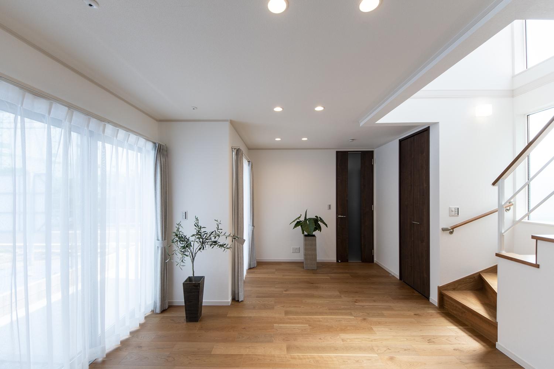 吹抜けから明るい光が差し込み、窓から自然な風が入り込む、明るく開放感のあるリビング。