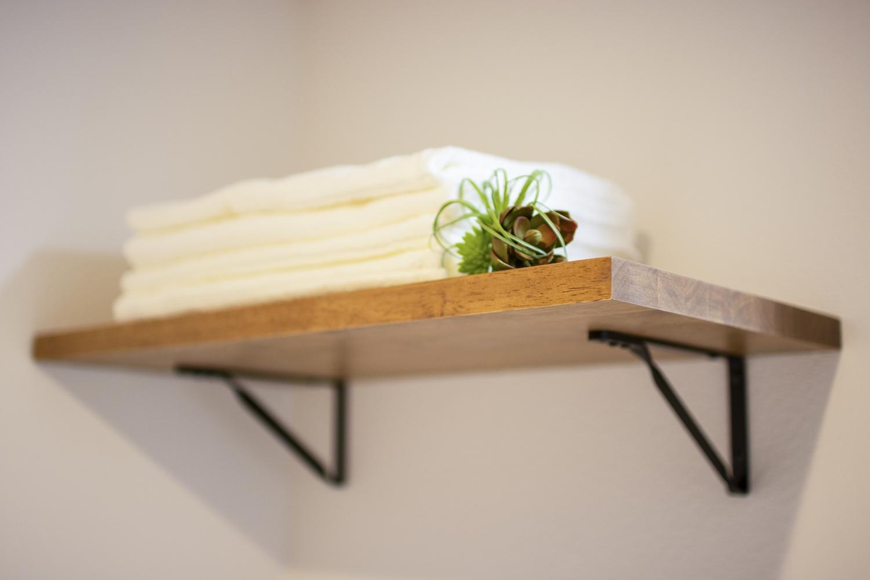 洗濯機置き場の上に、ラフな木目のシェルフを施しました。飾られたアイテムを引き立てます。