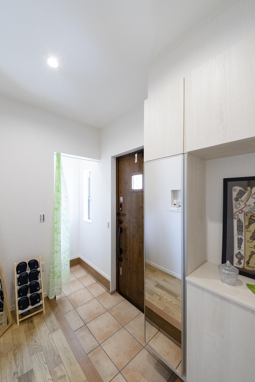 木の温もり感じる玄関ドアや収納、ベージュのテラコッタ調タイルがナチュラルな空間を演出します。
