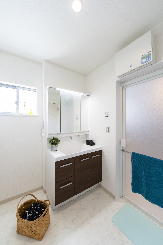 白を基調とした清潔感のあるサニタリールーム。石目柄の床が上質感をプラスします。