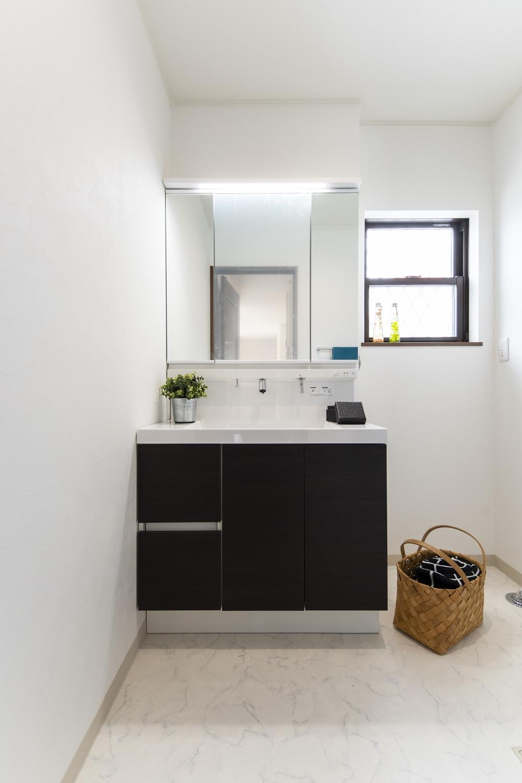 白を基調とした清潔感のあるサニタリールーム。洗面化粧台扉カラーをダークブラウンでアクセントにしました。