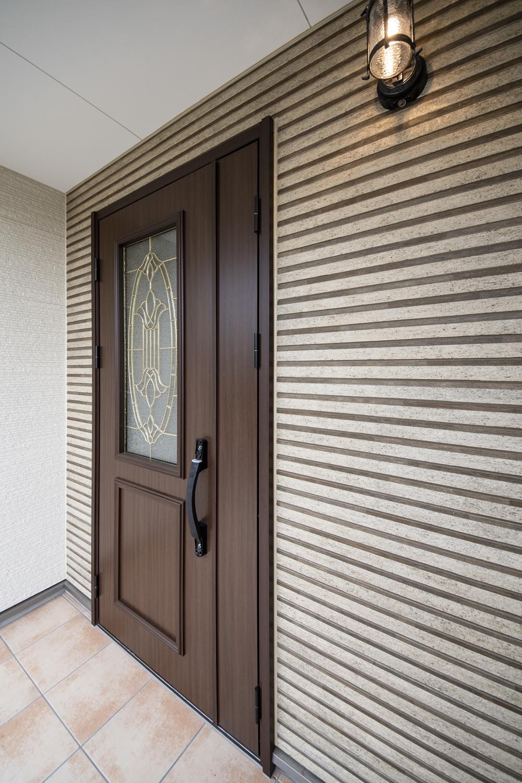 スタイリッシュなボーダーデザインの外壁に、ステンドガラスの玄関ドアを施した、おしゃれな洋風エントランス。