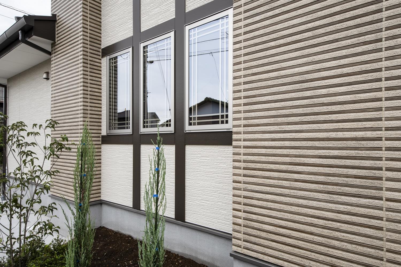 サイドに格子の入った窓を3連に並べた、おしゃれな洋風スタイル。