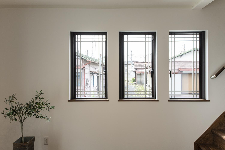 サイドに格子の入った窓を3連に並べた、洋風な雰囲気のおしゃれなリビング。