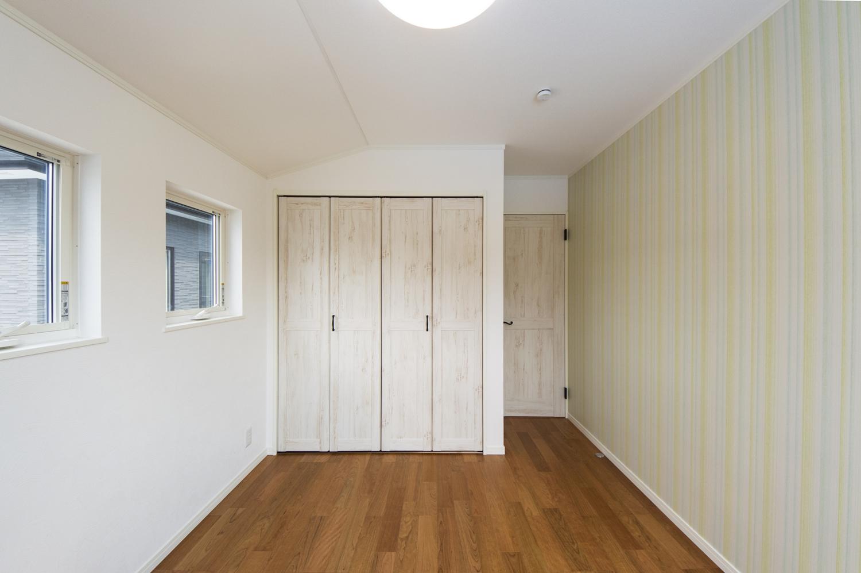 2階洋室/優しい色合いがきれいなストライプ模様の壁紙が、お部屋を明るく彩ります。
