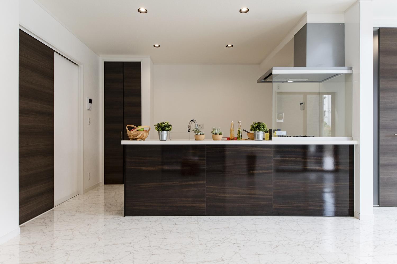 美しい光沢を放つダーク系木目カラーのペニンシュラ型キッチン。キッチン背面には扉付のパントリーを設置しました。