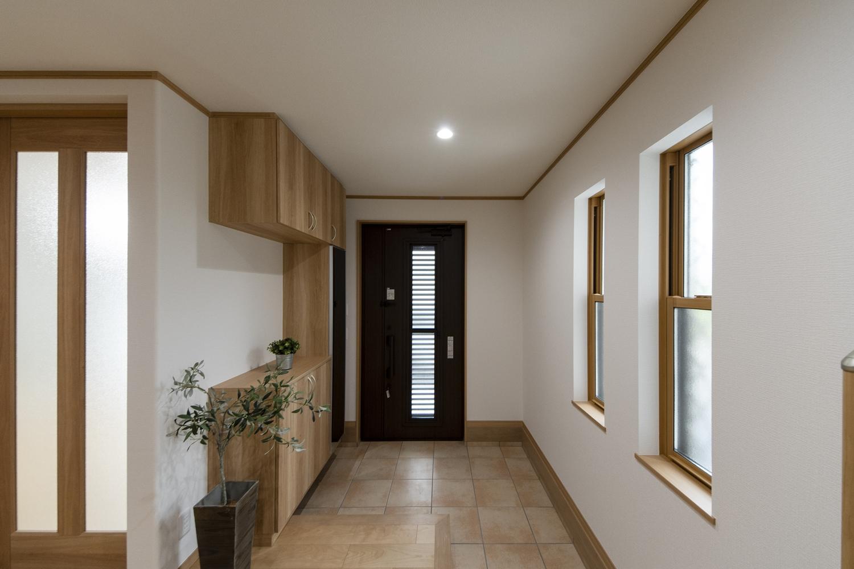 木の温もり感じる、明るくナチュラルな配色の玄関。窓から自然の光が差し込みます。