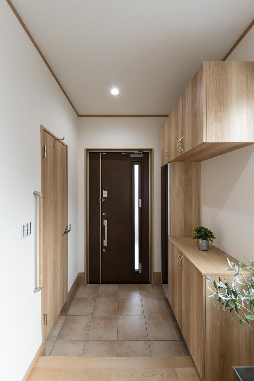 木の温もり感じる木目調のドアや収納、ベージュのテラコッタ調タイルが玄関をナチュラルな雰囲気に包みます。