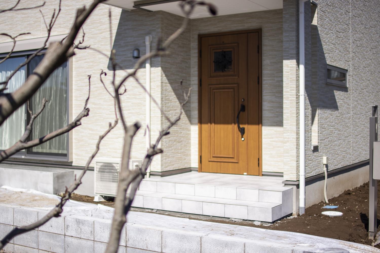 窓に鋳物飾りをあしらったエレガントなデザインの玄関ドアを施しました。