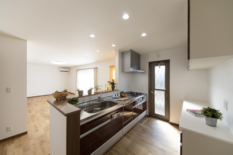 ダークブラウンのキッチン扉は、美しい光沢を放つ上品な木目デザインです。