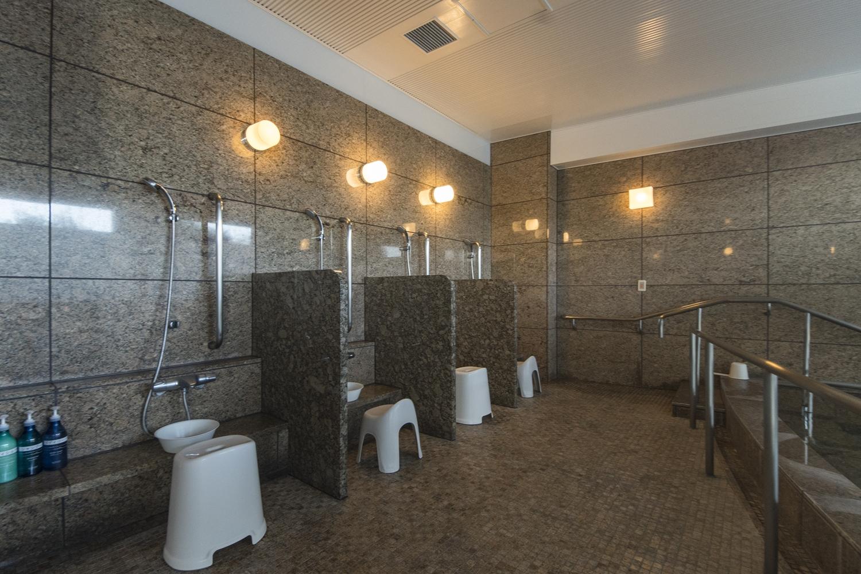 大浴場/転倒事故を防ぐため安全性に配慮して、手すりを設置しました。洗い場には隣者との仕切り壁を設置しました。