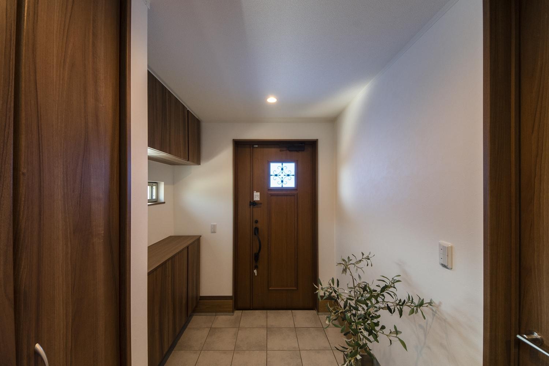 木の温もり感じるナチュラルテイストな玄関。窓に鋳物飾りをあしらったエレガントなデザインのドアを施しました。