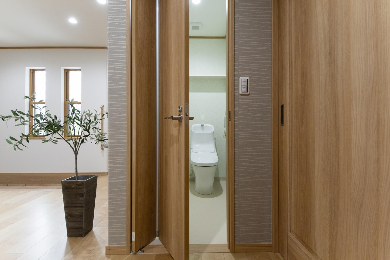 トイレ/立ち位置を変えずにドア本体を楽に開け閉めすることができる、折れ曲がり式のドアを設置しました。廊下にドアが飛び出さずにすみコンパクトです。