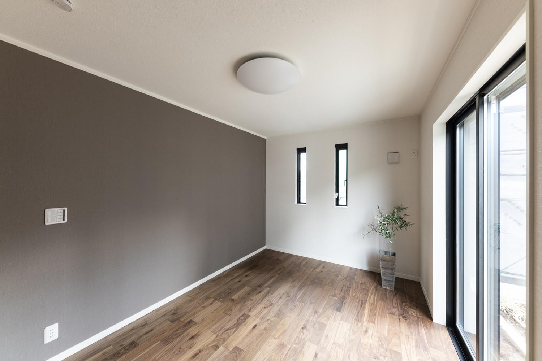 1階洋室/モノトーンカラーのクロスをアクセントにしたモダンな空間。