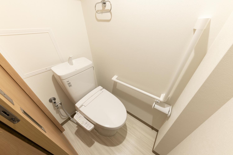 トイレ/白を基調とした清潔感のある空間に。手すりを設置して安全で快適な暮らしをサポートします。
