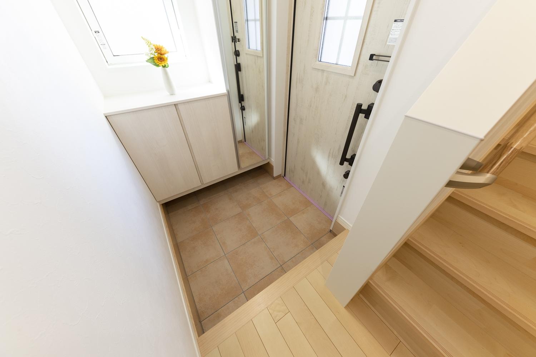 木の温もりを感じる玄関ドアと収納、ベージュのテラコッタ調タイルがナチュラルな空間を演出します。