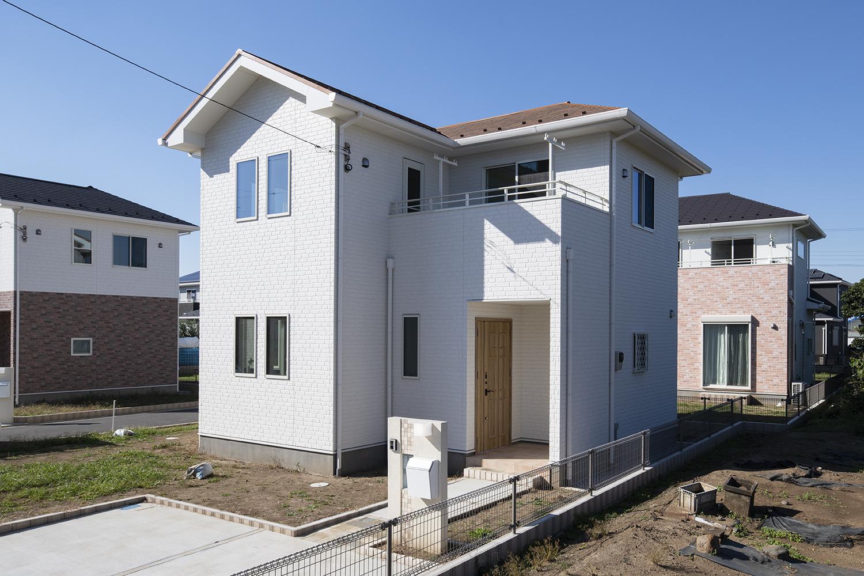 白いレンガ調の外壁にオレンジ色の屋根をあしらった、ナチュラル&モダンな外観。