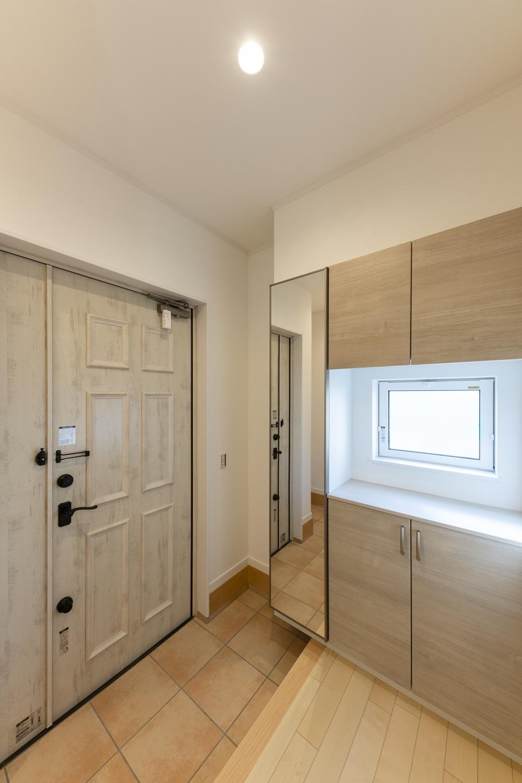 木の温もりを感じるナチュラルテイストな玄関。小窓から光が差し込む明るい空間です。