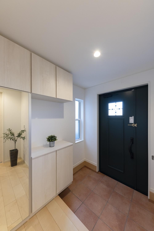 深みのあるグリーンの玄関ドアに、レッドのテラコッタ調タイルを施した、北欧風の温かみのある玄関。