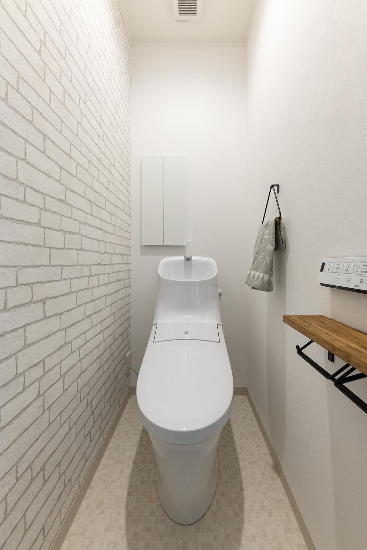 2階トイレ/レンガ調のクロスをアクセントにして木目カウンターのペーパーホルダーを施したおしゃれな空間。
