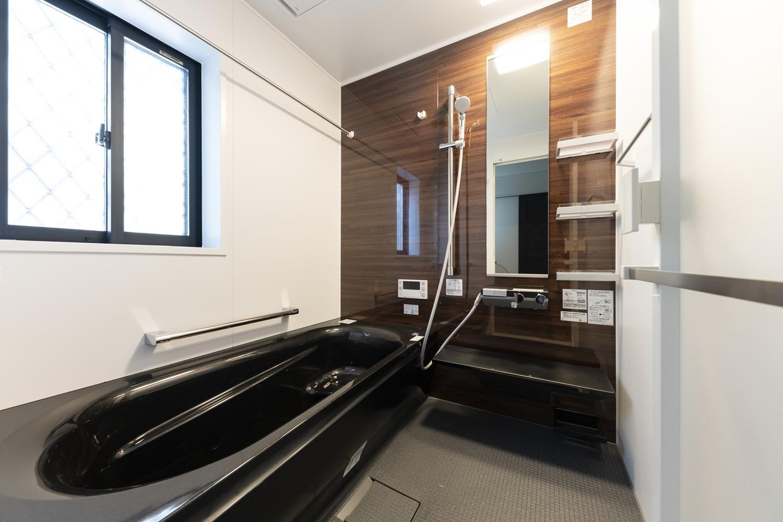 バスルーム/木目の豊かな表情をモチーフにしたアクセントパネルと、ブラックの浴槽が、上質な空間を演出します。