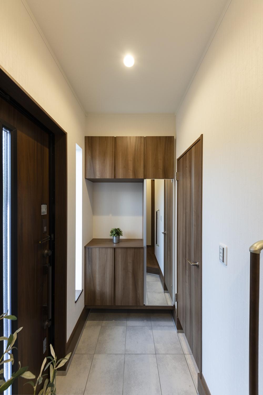 ダークトーンカラーの玄関ドア・玄関収納に、グレーのテラコッタ調タイルを合わせたシックでモダンな雰囲気の玄関に。
