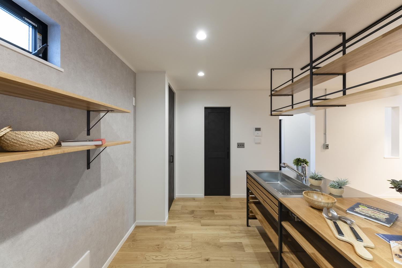キッチンの後ろにコンクリート調のクロスを貼ってアクセントをつけました。「飾る・使う・しまう」を楽しむ、おしゃれなカウンターも設置しました。