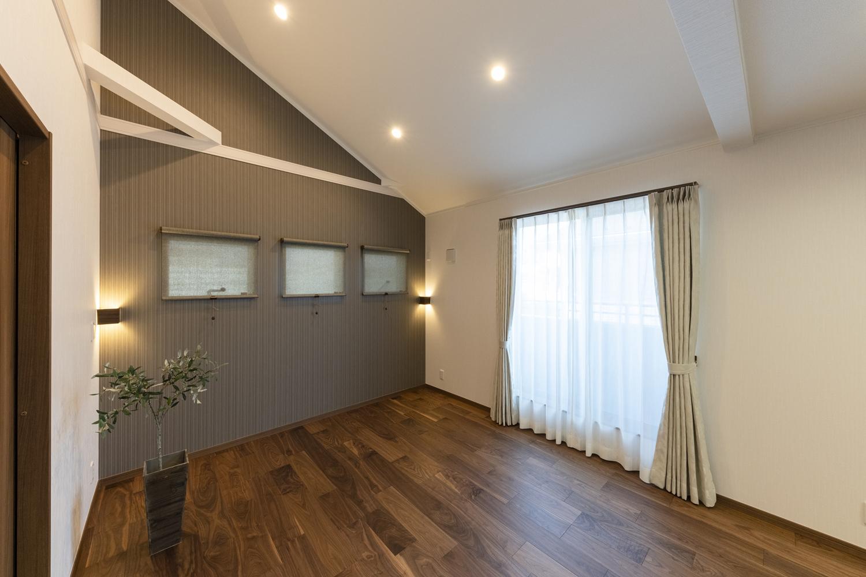 2階洋室/屋根の形に合わせて傾斜を持たせた勾配天井を設え、開放的な空間に。火打ち梁をあらわしにしてお部屋のアクセントにしました。