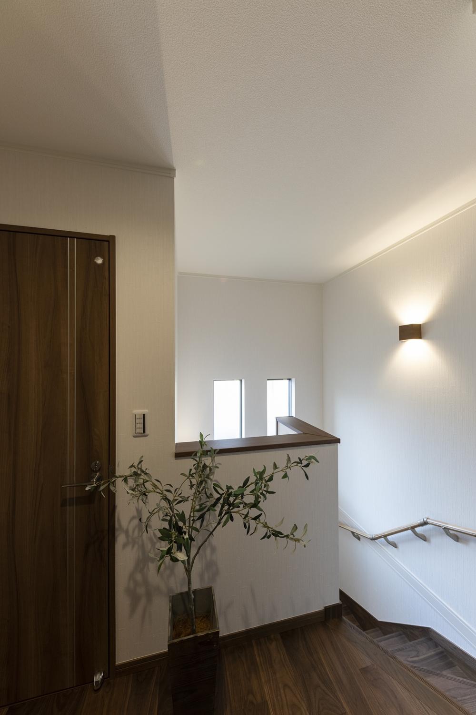 2階ホール/白い壁にダークトーンカラーの建具やフローリングを合わせた、シックでモダンな雰囲気の室内空間。