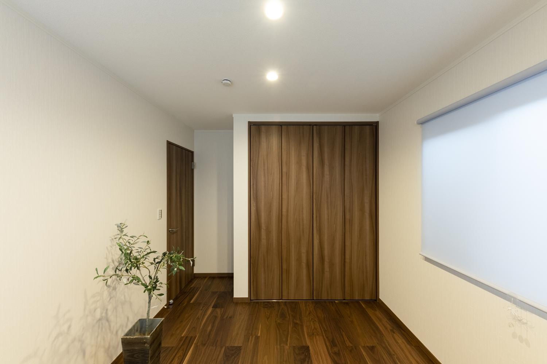 2階洋室/白い壁に深い色味の建具やフローリングを合わせた、重厚感のある室内空間。