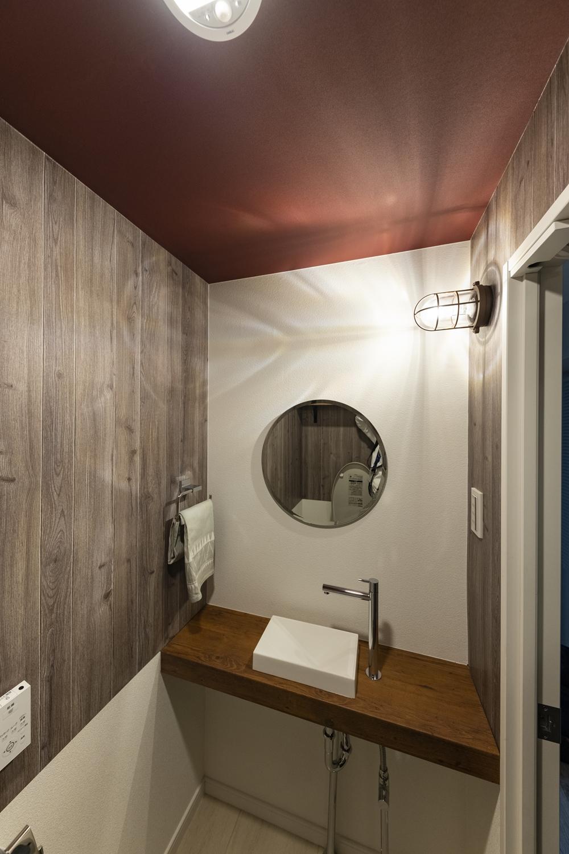 トイレ/木目調と無地のクロスを上下に張り分けた壁や、ボルドー色のクロスを施した天井、丸いミラーが、個性的で遊び心のある空間を演出。独立タイプの手洗いを設置してお客様をオモテナシします!