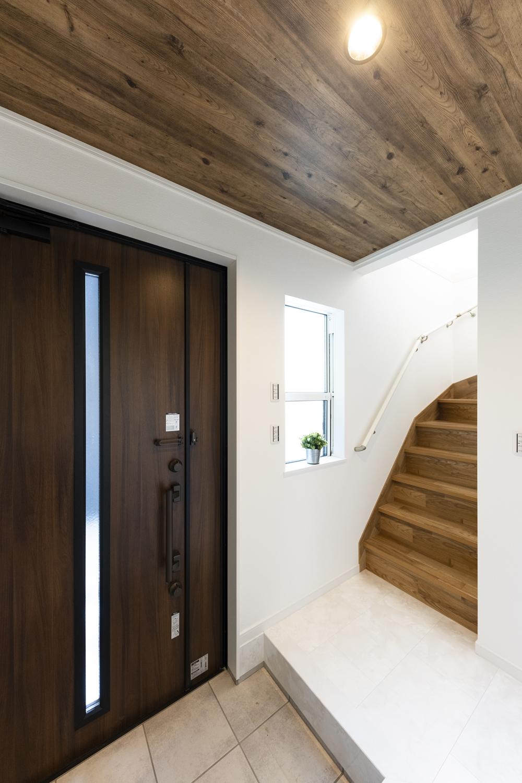 窓から光が差し込む明るい玄関。大理石の風合いをリアルに再現した白い化粧床材が、ラグジュラリーな空間を演出。