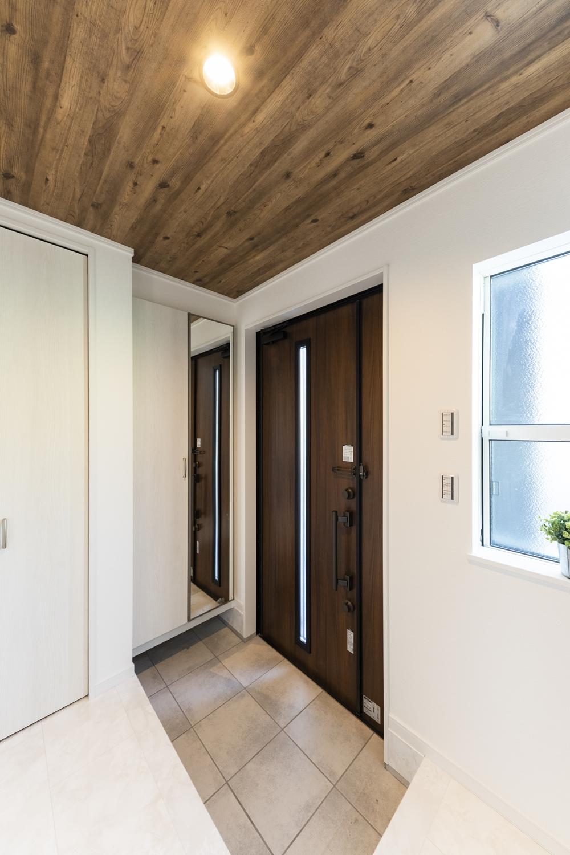 窓から光が差し込む明るい玄関。天井にも木目調クロスを施して木の温もりを感じる空間を演出しました。