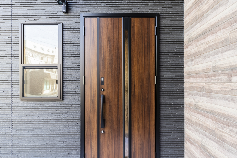 ブラックウォールナットにマットブラックのフレームを合わせた、重厚感のある玄関ドア。